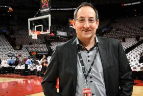 Dr. Howard Petroff smiles as he stands by the edge of the Raptors' basketball court.