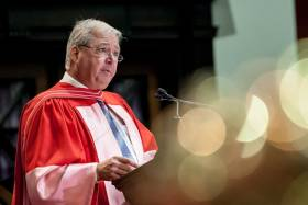 Carlo Fidani, wearing academic robes, speaks at a lectern in Convocation Hall.
