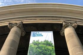 "A banner reading ""U of T Alumni Reunion"" hangs between pillars outside Convocation Hall. (photo by Kimberly Lyn)"