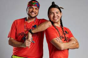 Anthony Johnson and James Makokis smiling. Makokis wears a feather and wrapped braids and Johnson wears a headband and necklace.