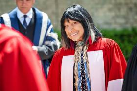 Buffy Sainte-Marie smiles mischievously as she looks through a crowd of dons, wearing academic robes.