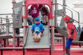 Children play on a slide made of parallel rollers, wearing T-shirts with the Jumpstart logo (photo courtesy of Canadian Tire Jumpstart Charities)