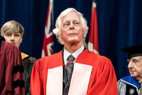 Ted Chamberlain looks serious as he stands on stage at Convocation in academic robes.