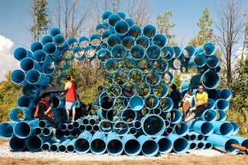 Visitors climb on the Futurity Island sonic artwork - dozens of massive water pipes piled three metres high like a 3D pan pipe.
