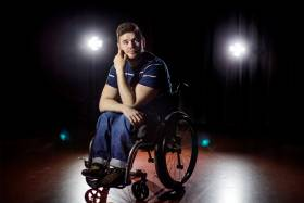 George Alevizos sits in his wheelchair, looking thoughtful, in the spotlight on a bare stage.