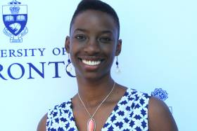 Janelle Joseph smiles while standing in front of a wall with the University of Toronto logo.