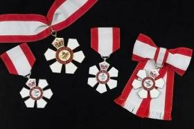 An array of several Orders of Canada - six-petaled silver medals with ribbons the colours of the Canadian flag.