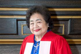 Setsuko Thurlow smiles, weating academic robes and standing against a wood-panelled wall.