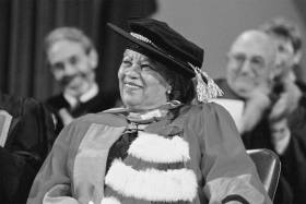 Toni Morrison smiles, wearing academic robes and a hat as she sits on stage at Convocation Hall after receiving an honorary degree.