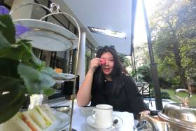 Joanna Luo smiles and holds a pink macaron cookie over one eye, while sitting at an outdoor cafe.