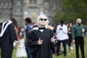 Elspeth Arbow makes finger guns as she stands on Front Campus in her academic robes and large sunglasses.
