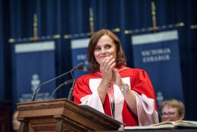 Judy Goldring smiles and claps as she stands at a podium, wearing academic robes.
