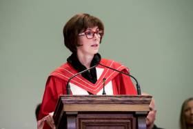 Katie Taylor, wearing academic robes, speaks at a lectern.