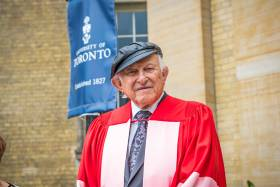 Nate Leipziger, wearing academic robes and his trademark leather cap, stands outside Convocation Hall.