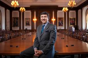 David Naylor smiles while leaning on a  polished conference table in a large boardroom, decorated with painted portraits and old-fashioned chairs.