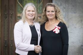 Susan Chatwood and Julie Payette smile as they shake hands. Both women are wearing medals.