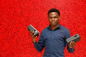 Olugbenga Olubanjo holds up two small rectangular plastic capsules with the Reeddi logo and plug sockets on the end.