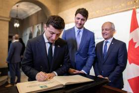 Volodymyr Zelenskyy signs U of T's guest book Prime Justin Trudeau and  Meric Gertler look on.