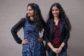 Identical twins Sandhya and Swapna Mylabathula stand side by side, smiling and laughing  (photo by Geoffrey Vendeville)