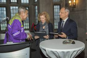 Elder Andrew Wesley, wearing formal Indigenous regalia, hands binders to Cheryl Regehr and Meric Gertler by a table holding a sacred abalone shell (photo by Johnny Guatto)