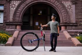 "Taylor Stark, a U of T alumnus who is returning for a master's degree in classics, rode his unicycle ""Caroline"" from Vancouver to Toronto (photo by Geoffrey Vendeville)"