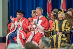 Mark Tewksbury grins and applauds while sitting on stage at Convocation Hall with Rose Patten, wearing academic robes.