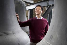 Carillonneur Roy Lee stands between giant bronze bells, smiling. (Image by Michelle Yee Photography.)