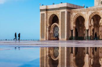 Two people walking outside Hassan II Mosque, Casablanca