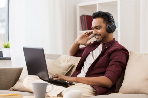 Man sits on couch using laptop and listening through headphones, smiling