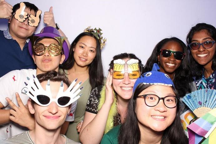 A group of young alumni in fun costumes smiling and posing in front of a lavender background