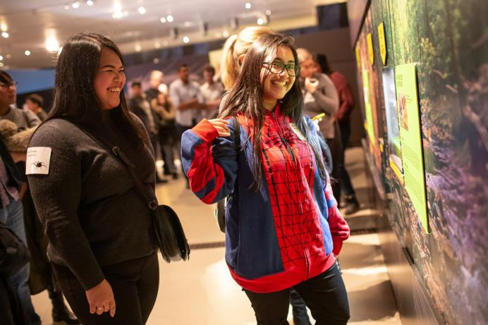 female guest showing off her Spiderman sweater shirt while looking at an exhibit