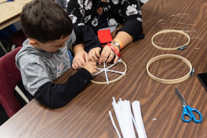 Child building an artificial spider's web
