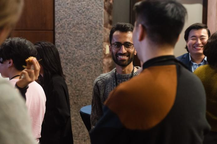 An alum laughs in conversation with other alum at networking night