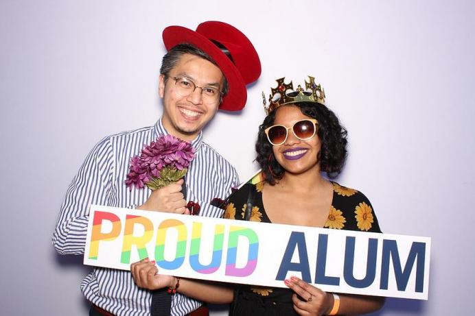 Two alum in fun costumes smiling and posing with PROUD ALUM sign in front of a lavender background
