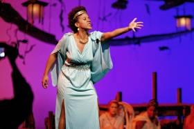 Actress in Grecian gown gesturing passionately on stage at Hart House Theatre