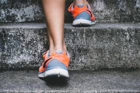 Closeup of jogger's feet in running shoes going up steps