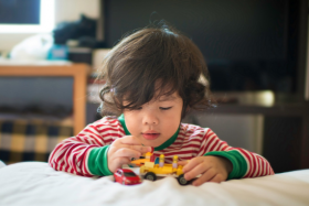 Child playing with a toy truck and car on a bed.