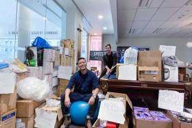 Two young male students in a room full of boxes of supplies.