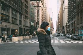 a woman crossing an empty, urban street wearing a surgical mask