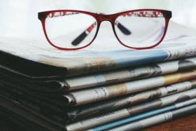 a pair of reading glasses sitting on a stack of newspapers