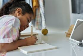 girl writing on white paper at a desk with a tablet