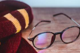 A burgundy and yellow striped scarf beside a pair of round, black-framed glasses on a wooden desk.