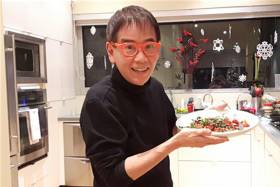 John Ota holding a dish of food in a kitchen