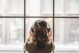 Woman listening to headphones and looking out a wall of windows