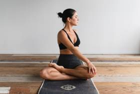 A woman, sitting on a mat, holding a yoga pose.