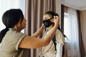Woman puts face mask on young girl with backpack