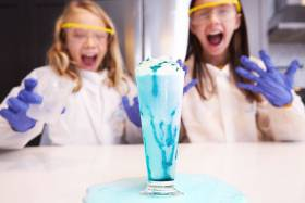 Two young girls in lab coats, gloves and visors stand in front of a tall glass with blue liquid