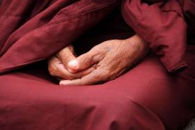 Monk sits with hands together on lap