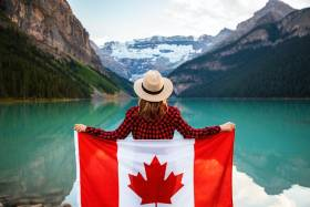 Woman stands facing the lake holding the Canadian Flag behind her back
