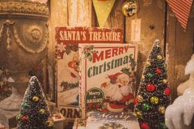 Two hardcover books with Santa on cover sit on table with two small Christmas trees and other decorations